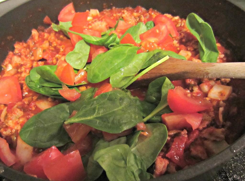 adding spinach to spaghetti sauce