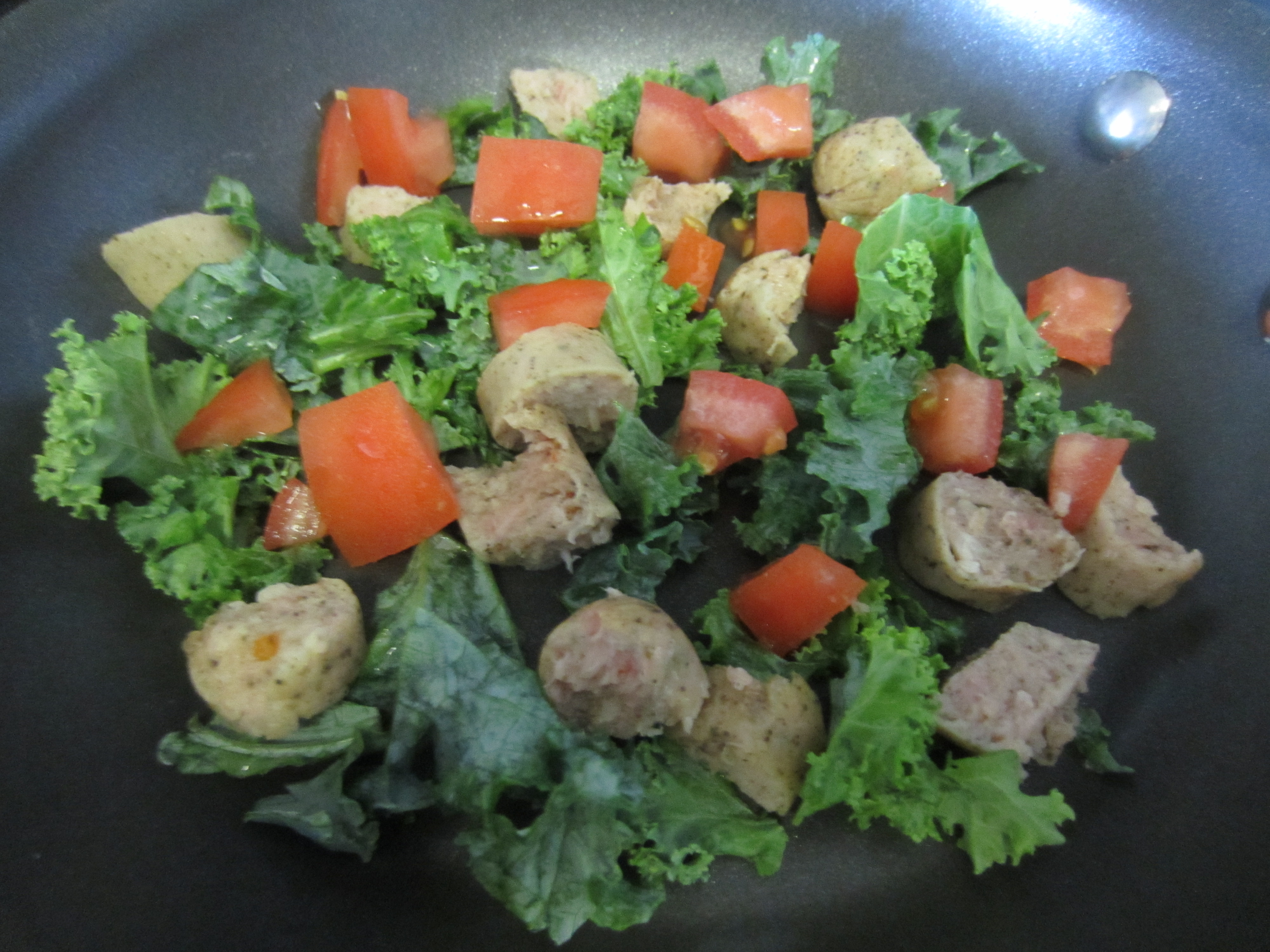 scrambling kale tomato and chicken sausage in eggs