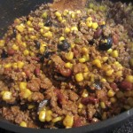 adding ingredients to chili