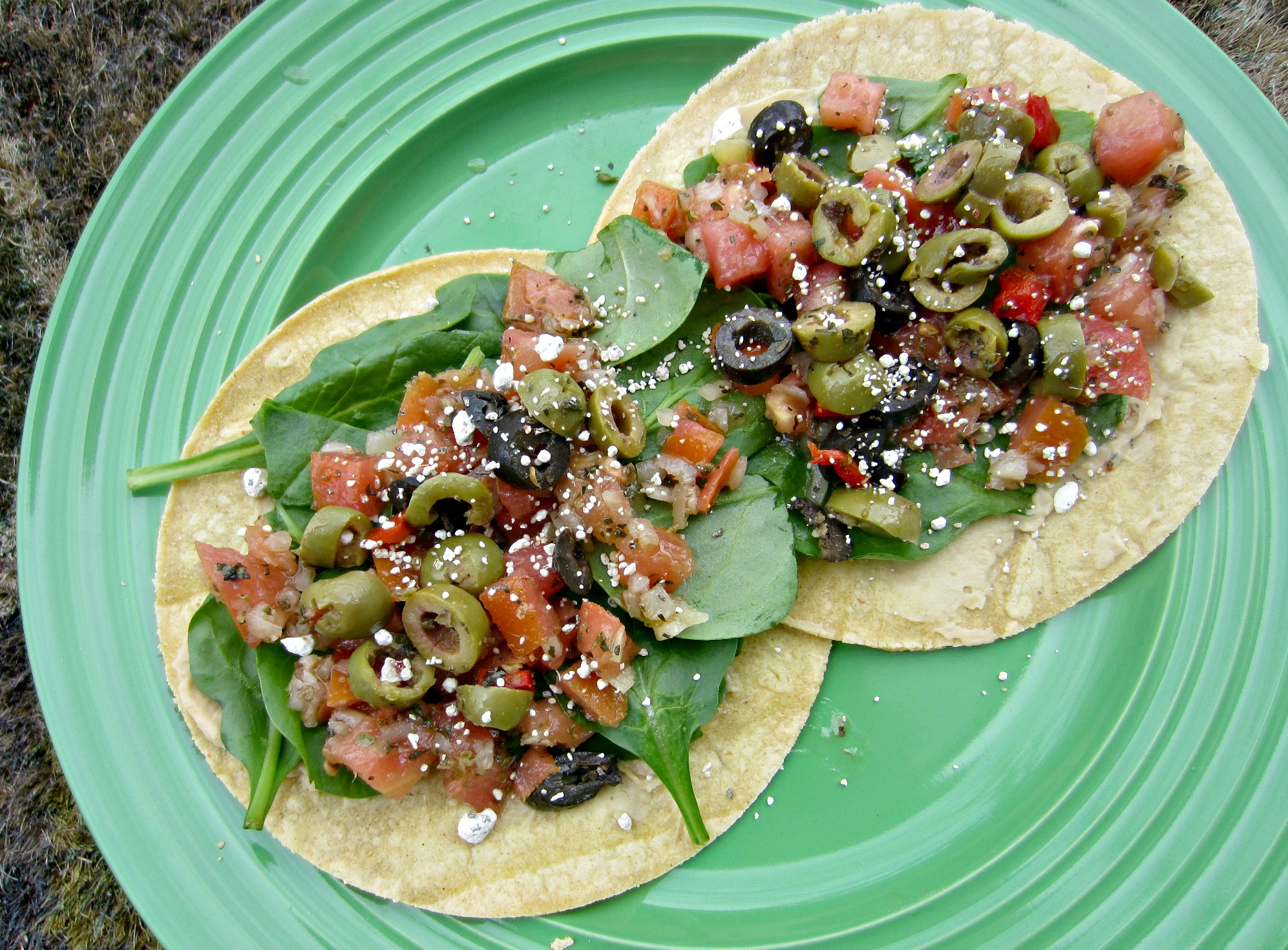 olive and mediterranean bruschetta with spinach on corn tortillas