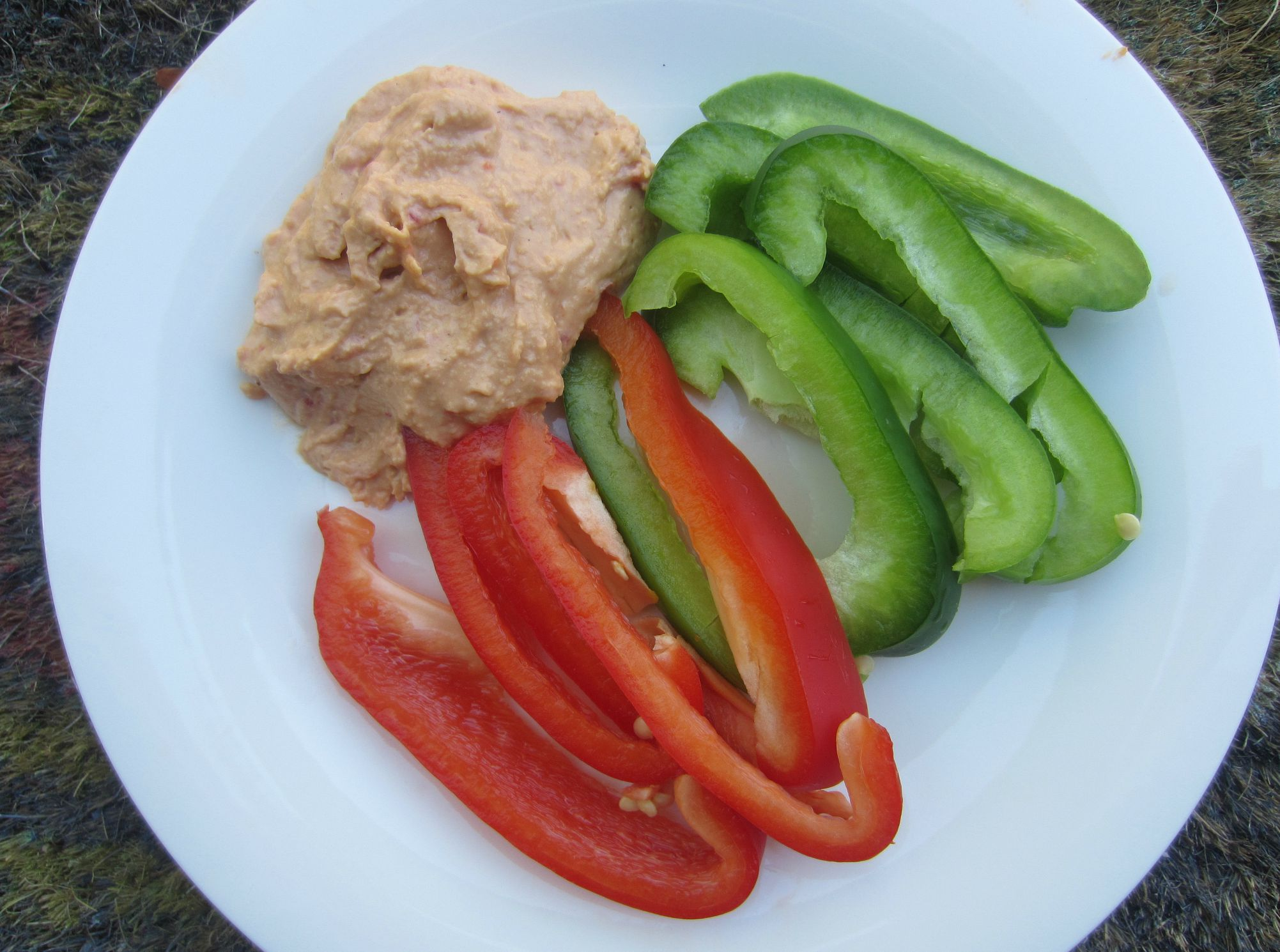 sliced red and green peppers with red pepper hummus