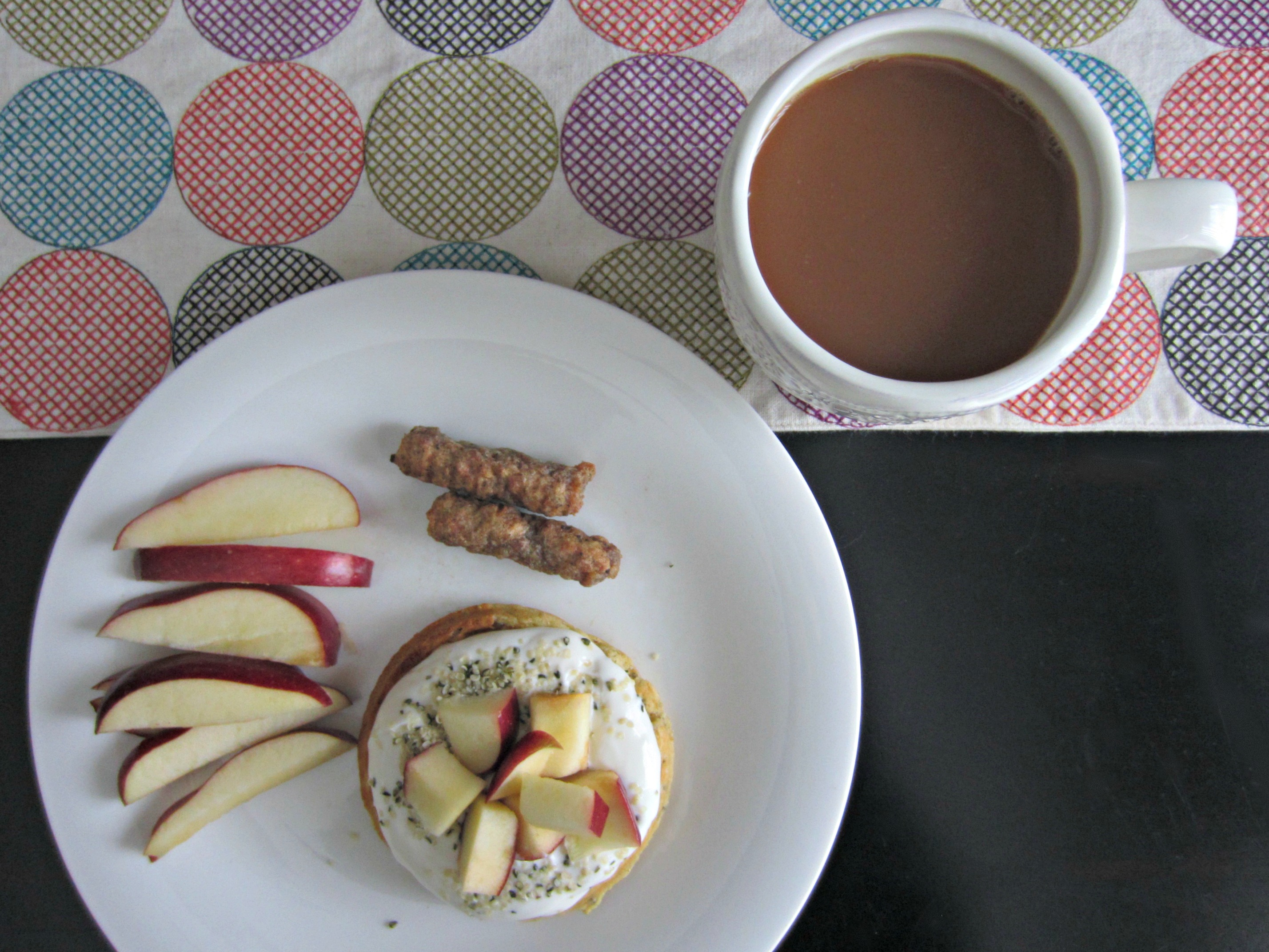 healthy breakfast with waffle, greek yogurt, chicken sausage, and apples