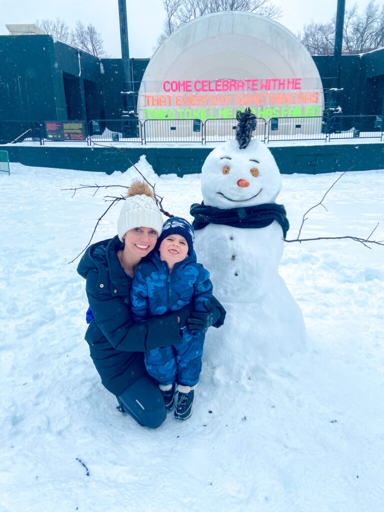 Skyler and Heather with snowman in the park